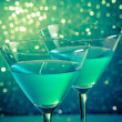 Glasses of blue cocktail on dark green tint light bokeh — Stock Photo