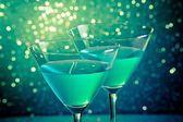 Glasses of blue cocktail on dark green tint light bokeh — Stock Photo
