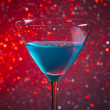 One glass blue cocktail on red tint light background — Stock Photo