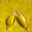 Champagne flutes with golden bubbles on golden light bokeh background — Stock Photo