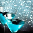 A pair of glasses of fresh blue cocktail with ice on bar table — Stock Photo