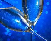Champagne flutes on blue light bokeh background — Stock Photo