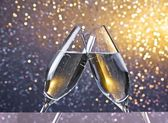 Two champagne flutes with golden bubbles on light bokeh background — Stock Photo