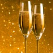 A pair of flutes of champagne on golden abstract background — Stock Photo