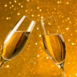 Two champagne flutes with golden bubbles on golden light bokeh background — Stock fotografie