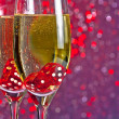 Stock Photo: Red dice dropping in champagne flutes on red and violet tint light bokeh background