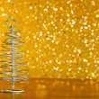 Metallic modern christmas tree on wood table on golden tint light bokeh background — Stock Photo