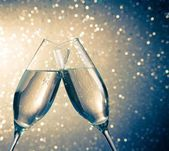 Champagne flutes with golden bubbles on blue light bokeh background — Stock Photo