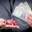 Stock Photo: Toy car and dollars in hands of business mconcept for insurance, buying, renting, fuel or service and repair costs