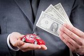 Toy car and dollars in the hands of business man concept for insurance, buying, renting, fuel or service and repair costs — Stock Photo
