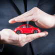 Businessman protect with his hands a red car, concept for insurance, buying, renting, fuel or service and repair costs — Stock Photo #38186325