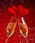 Two champagne flutes with golden bubbles and red velvet hearts make cheers on red bokeh background — Stock Photo