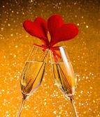 Two champagne flutes with golden bubbles and red velvet hearts make cheers on golden bokeh background — Stock Photo