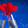 Stock Photo: Two champagne flutes with golden bubbles and red velvet hearts make cheers on blue bokeh background