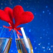 Two champagne flutes with golden bubbles and red velvet hearts make cheers on blue bokeh background — Stock Photo