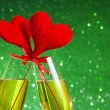 Two champagne flutes with golden bubbles and red velvet hearts make cheers on green bokeh background — Stock Photo #38672703