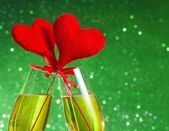 Two champagne flutes with golden bubbles and red velvet hearts make cheers on green bokeh background — Stock Photo