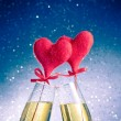 Stock Photo: Champagne flutes with golden bubbles and red velvet hearts make cheers on blue bokeh background