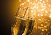 香槟笛子与金色的泡泡,暗金色光散景背景上的细节 — 图库照片