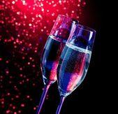 Champagne flöjter med gyllene bubblor på mörk blå och violett ljus bokeh bakgrund — Stockfoto