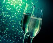 Champagne flutes with golden bubbles on dark green light bokeh background — Stock Photo
