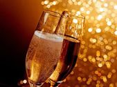 Detail of champagne flutes with golden bubbles on warm light bokeh background — Stock Photo