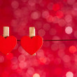 Two decorative red hearts hanging against red light bokeh background, concept of valentine day — Stock Photo