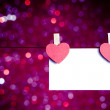 Two decorative red hearts with greeting card hanging on blue and violet light bokeh background, concept of valentine day — Stock Photo
