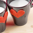 Stock Photo: Cups of milk with decorative hearts on wood table, concept of valentine day