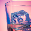Glass of drink with ice on disco violet light — Stock Photo