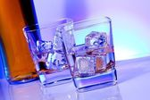 A pair of glasses of alcoholic drink with ice on disco blue light — Stock Photo