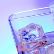 Glasses of alcoholic drink cocktail with ice on disco blue light — Stock Photo