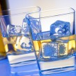 Two glasses of whiskey with ice on blue light — Stock Photo