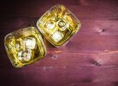 Top of view of two glasses of whiskey with ice on old wood table background  — Stock Photo