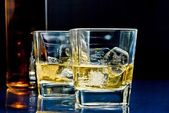 Two glasses of alcoholic drink with ice on disco blue light — Stock Photo