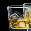 Two glasses of alcoholic drink with ice on black background — Stock Photo