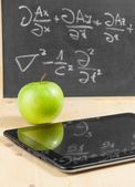 Tablet pc and green apple in front of blackboard on wood table — Stock Photo