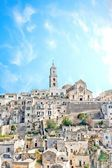Panoramic view of tipical stones and church of Matera under blue sky — Stock Photo