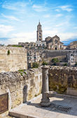 Panoramic view of tipical water dispenser and church of Matera under blue sky — Stock Photo