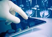 Hand in medical blue glove touching modern digital tablet on x-ray images background — Foto Stock
