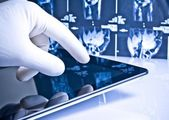 Hand in medical glove touching modern digital tablet on x-ray images background — Stock Photo