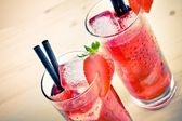 Two glasses of strawberry cocktail with ice on old wood table, old style — Stock Photo