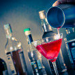 Barman pouring a red cocktail into a glass with ice — Stock Photo #47300427