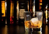 Whiskey glass with ice in front of bottles — Stock Photo