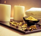 Spa massage border background with towel stacked, perfumed leaves, candle and sea salt — Stock Photo