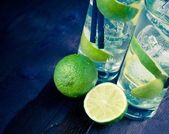Detail of two glasses with cocktail and ice with lime slice on old wood background — Stock Photo