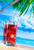 Glasses of red cocktail with blur beach and palm — Zdjęcie stockowe