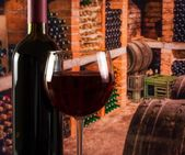 Red wine glass near bottle on old wine cellar background with space for text — Stock Photo