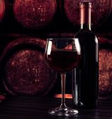 Red wine glass near bottle on wood table and in old wine cellar background — Stock Photo