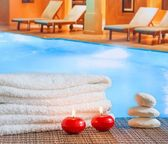 Spa massage border background with towel stacked,red candles and stone near swimming pool — Stock Photo